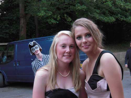 guy wearing pirate hat and mask photobombs two girls at prom