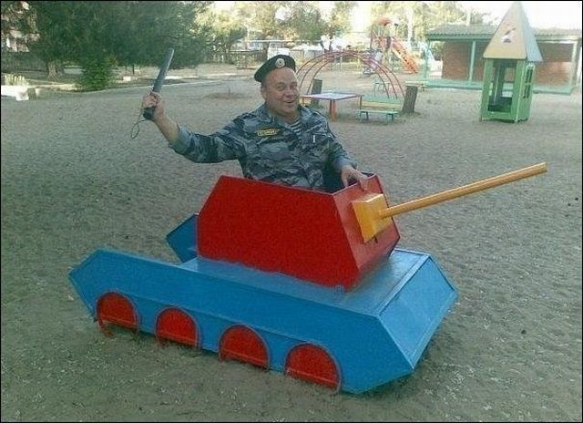 man in army uniform sitting in playground toy tank, lol