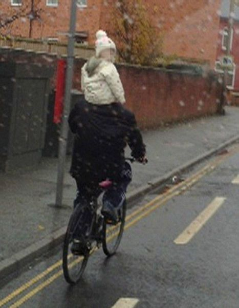 man dangerously rides bicycle with baby on shoulders, parenting fail, wtf, stupid
