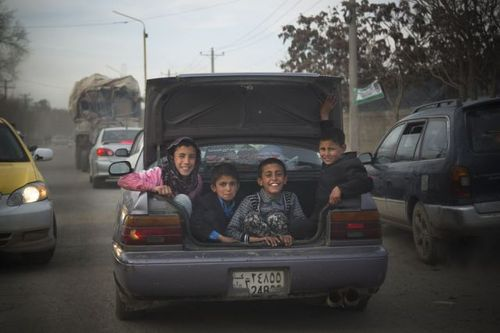 four kids riding in a car trunk