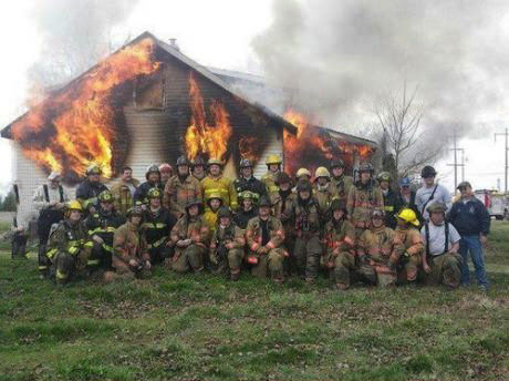 firemen posing for picture in front of burning house, wtf