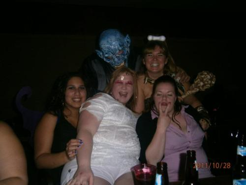 large women at a bar photobombed by blue demon creature, wtf