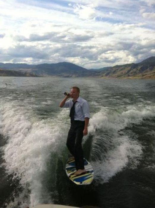 guy in formal clothing surfs and drinks a beer behind a boat in a lake under beautiful mountains