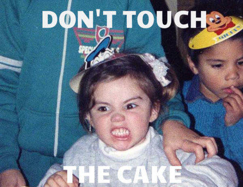 don't touch the cake, kid with angry look on her face