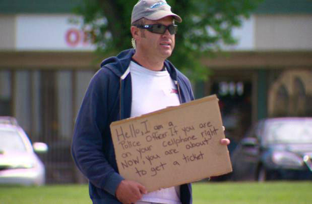 homeless sign, cellphone, police officer, troll