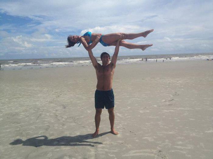 guy lifts girl on beach and makes a centaur shadow