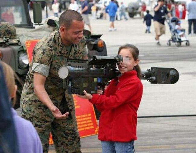 little girl holding a grenade launcher