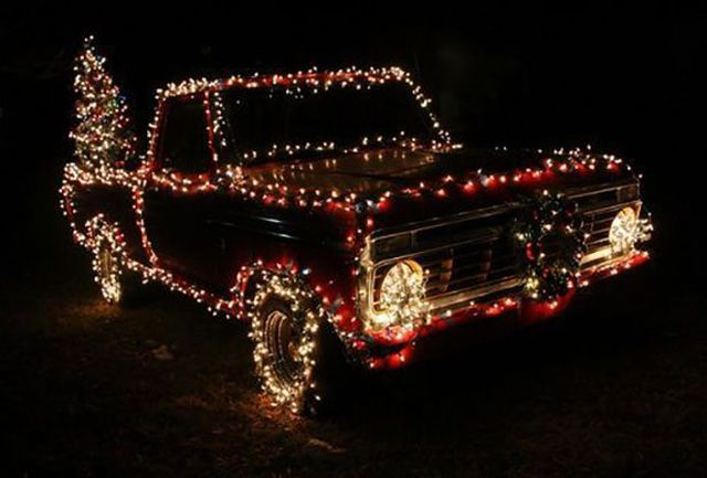 a truck with christmas lights on it and a tree in the back