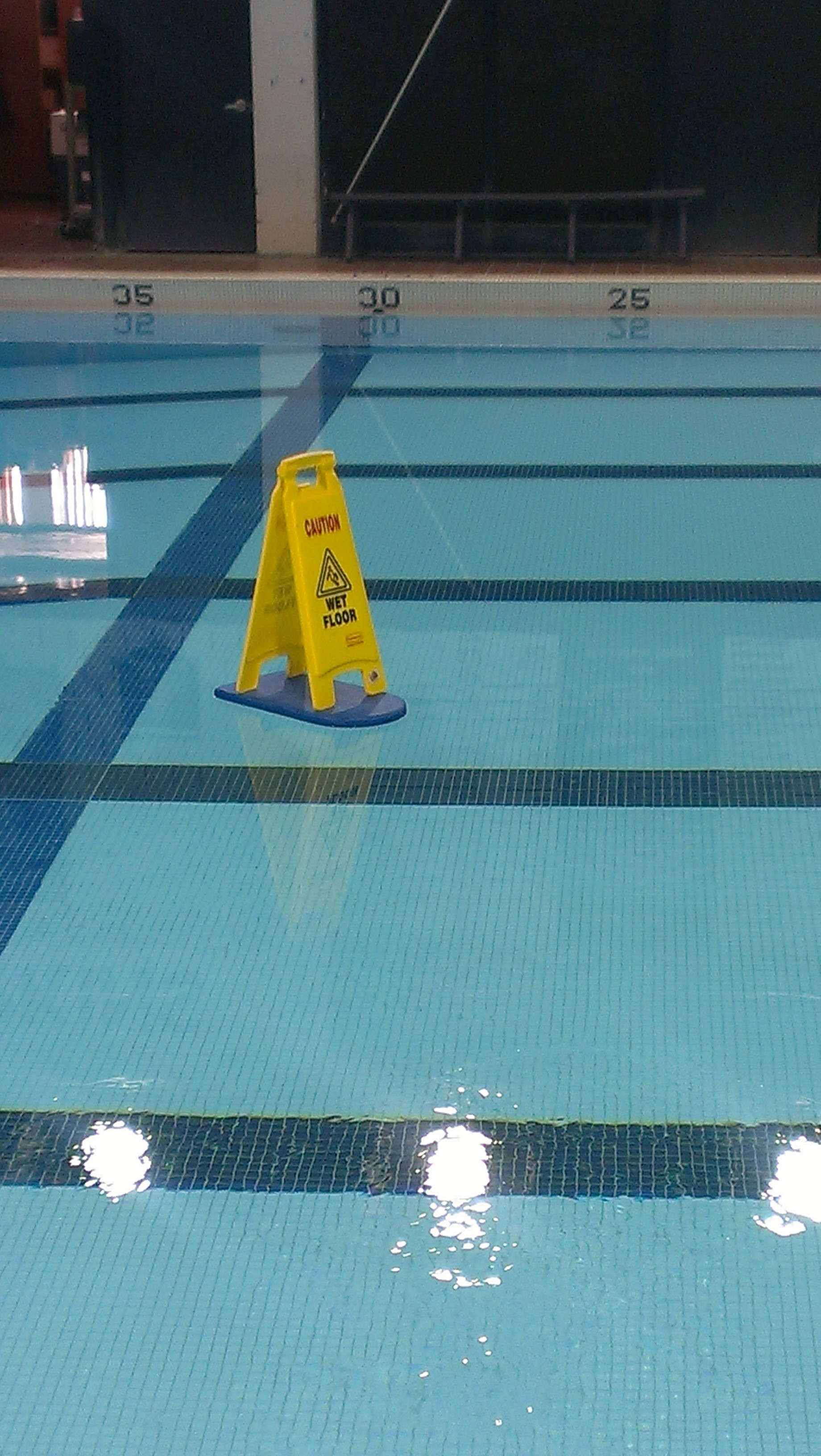 caution, wet floor sign floating on a raft in a swimming pool, lol