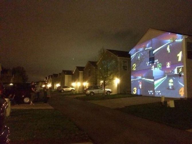 playing mario kart on the side of a house, projector, nintendo, win