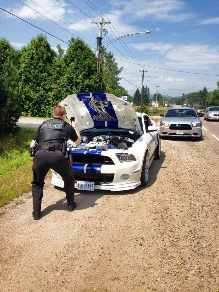 not the worst reason to be pulled over by a cop, police officer taking picture of muscle car engine