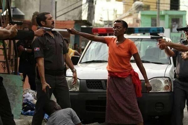 the most raw photo of the week, haitian woman protecting her son with a knife the a cop's throat