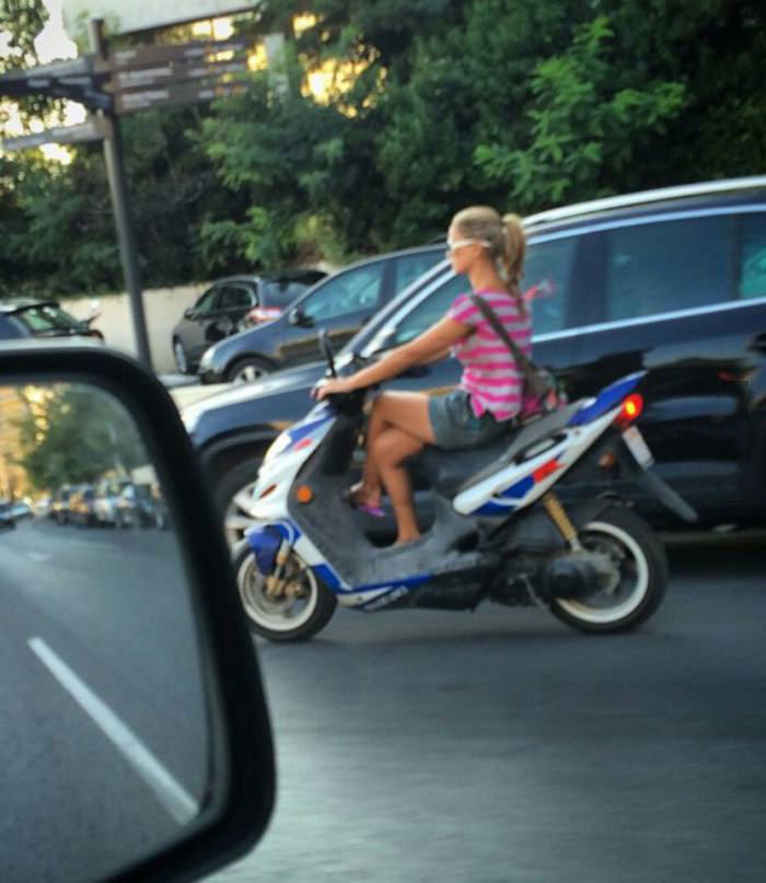 crossed legged riding a scooter, woman from greece are very elegant drivers