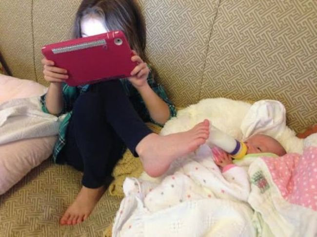 when kids help out around the house, daughter holding baby bottle with her foot while on a tablet, cute kids