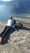 oh my god look at those buildings they must be huge, girl lying down with view of water and land off cliff