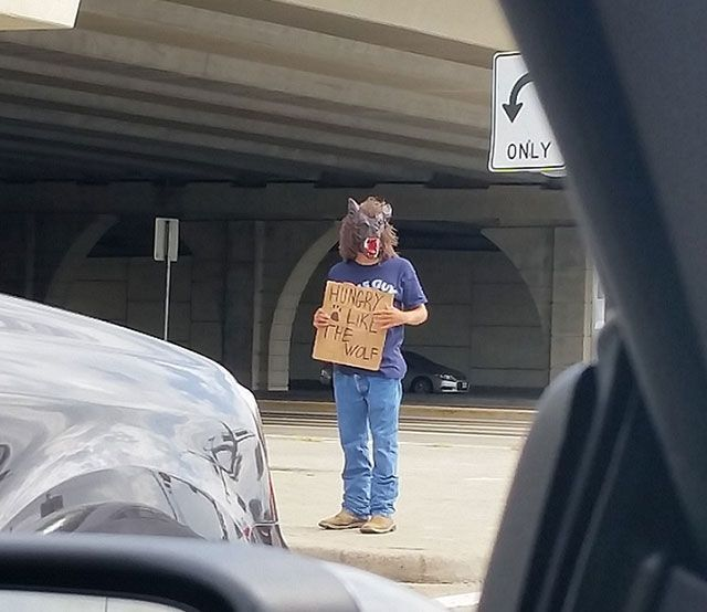 hungry like the wolf, homeless man waring wolf mask holding sign