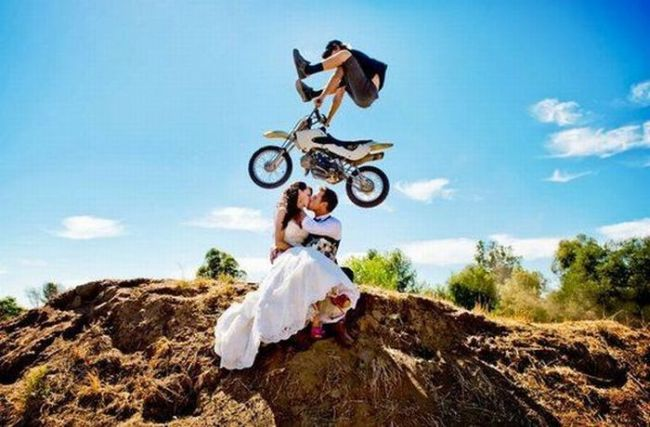 epic wedding photo, married couple kissing with dirt bike rider in mid air