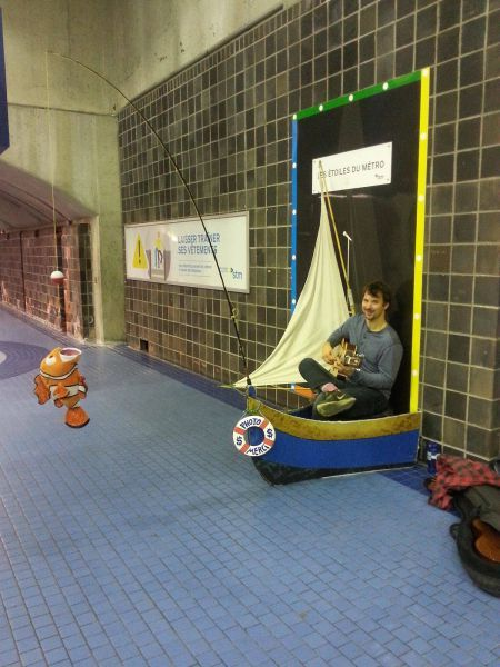 street performer in the montreal metro system in a little boat fishing for change