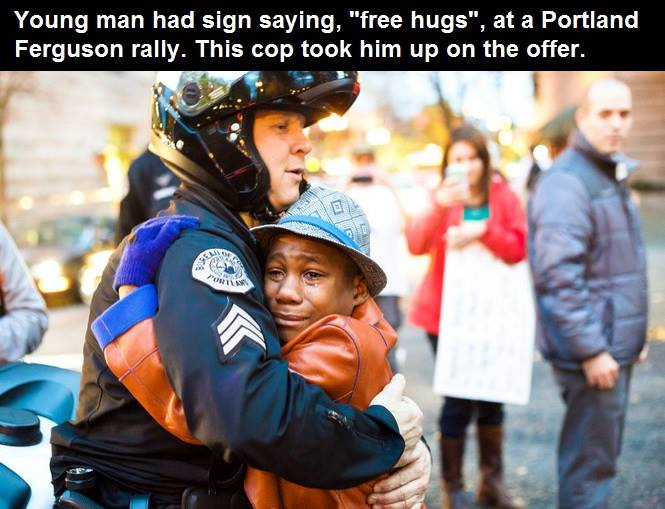 young man had sign saying free hugs at a portland ferguson rally, this cop took him up on the offer, beautiful moment