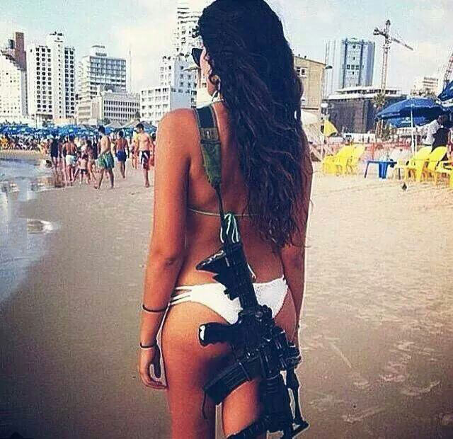 female israeli police officer on the beach with a rifle