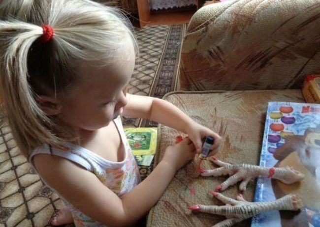 little girl painting nails on rubber chicken legs