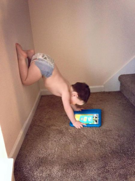 kid playing on game tablet in a strange position, legs on wall