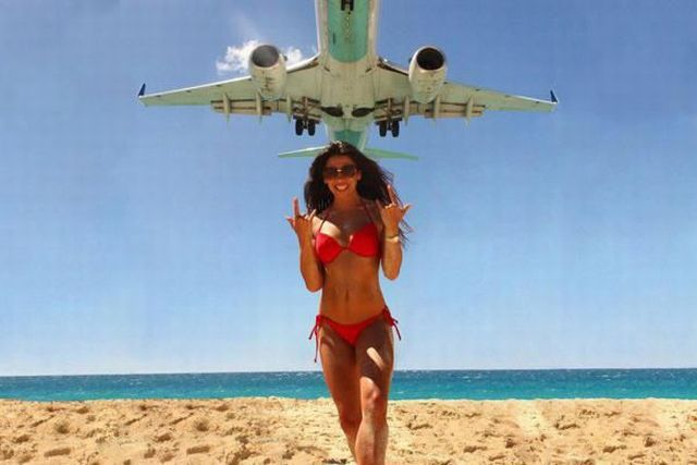 girl in bikini happy to be on the beach photobombed by low flying plane