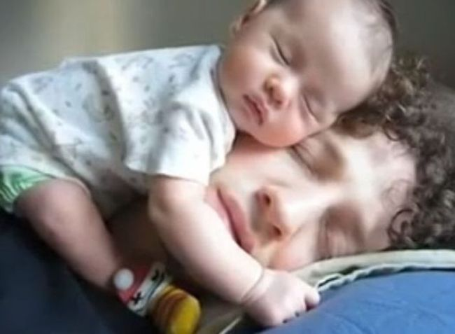 baby sleeping on father's face