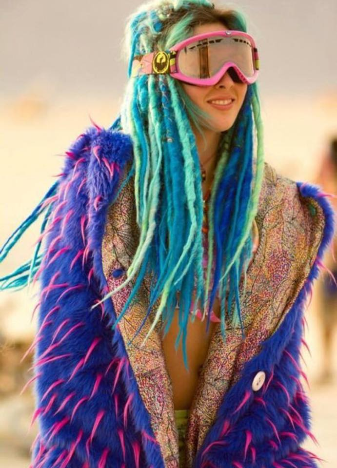 natural born raver, really colourful rave girl with purple jacket green and teal dreads and ski goggles