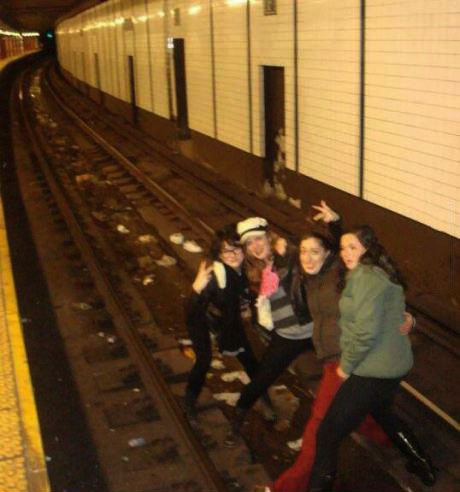four girls posing on subway tracks, stupid