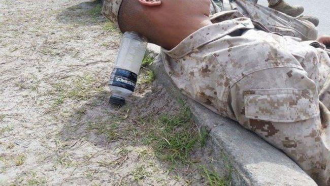 soldier resting his head on a water bottle