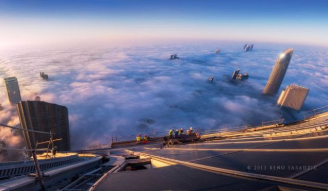 view of a city from above the clouds in a skyscraper