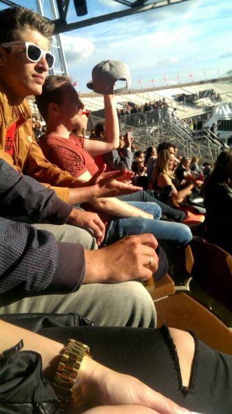 guy in stadium using his baseball cap to block the sun
