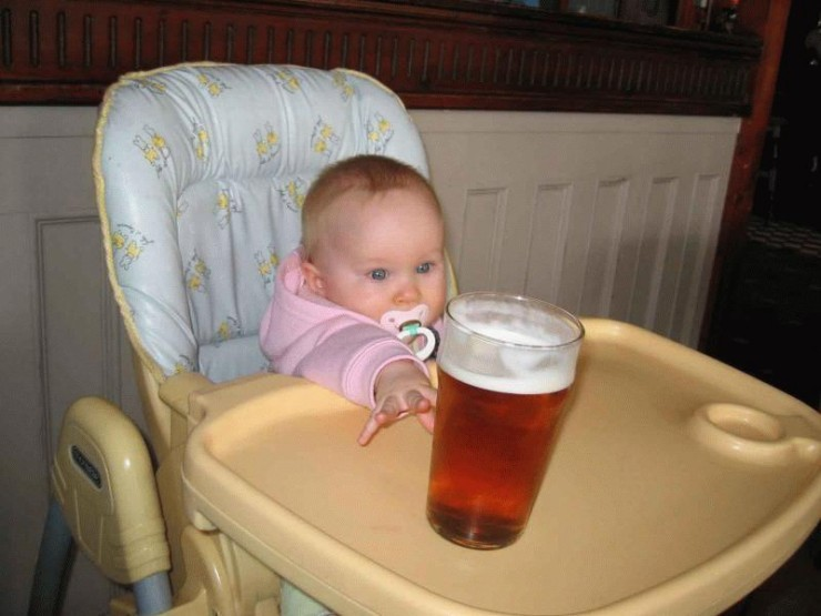 baby in high chair reaching for beer with intent look in eyes