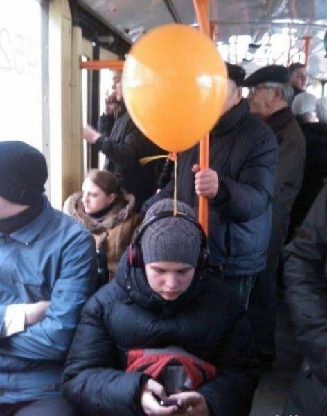 balloon tired to headphones on public transportation