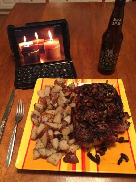a romantic dinner for one, candles burning on a laptop screen, stone ripa, steak and fried potatoes