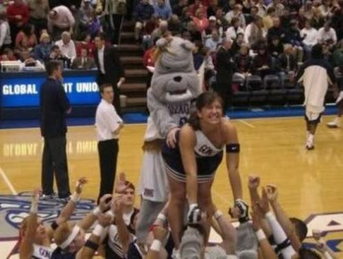 awkward cheerleading moment, bulldog mascot mounts cheerleader in air at basketball game