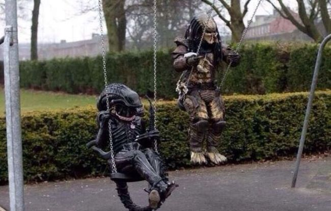 alien and predator sharing a swing set, enemies now best friends forever