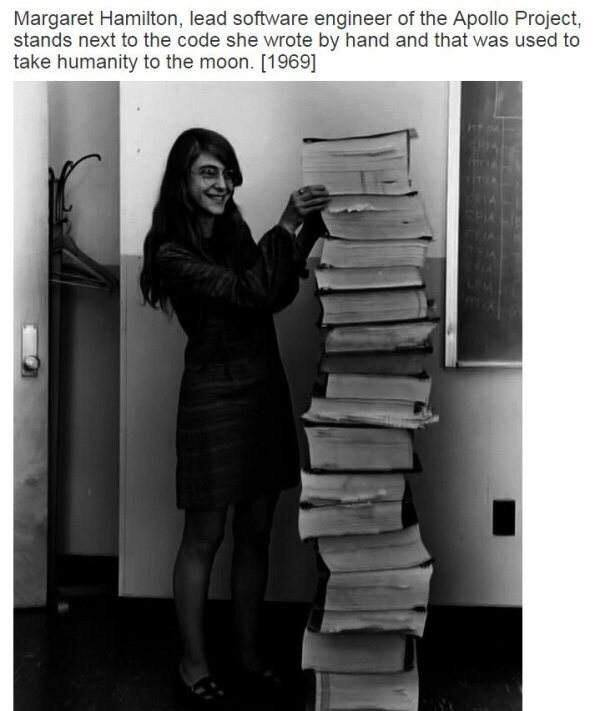 margaret hamilton, lead software engineer of the apollo project,  stands next to code wrote by hand and that was used to take humanity to the moon in 1969