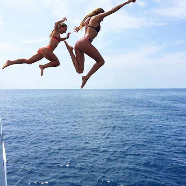 two girls in bikinis jumping into the water
