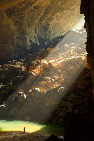 sunlight shining into a giant cave opening, nature