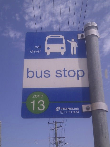 what neighbourhood is this bus stop in, and why are the bus and the person both white?, hail driver, awkward arm gesture, politically incorrect bus stop