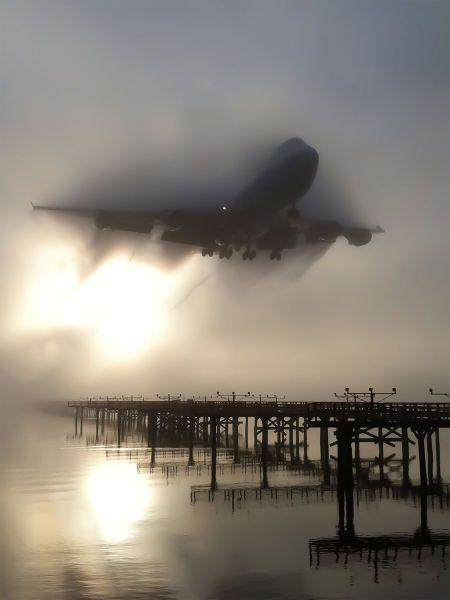 plane landing over foggy beach