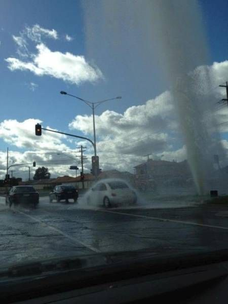 when skies are sunny but it's raining on you, broken fire hydrant soaking car