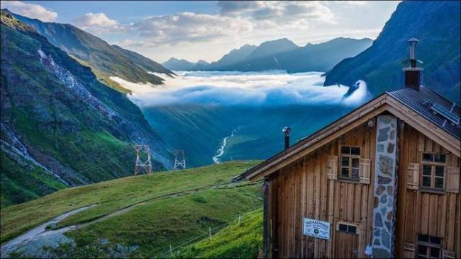 epic view of a valley under low clouds from mountain top cottage