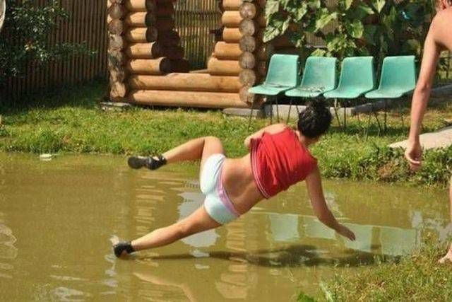 perfectly timed photograph of girl galling into muddy pond