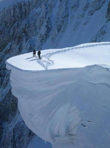 two people standing on top of a huge snow ledge