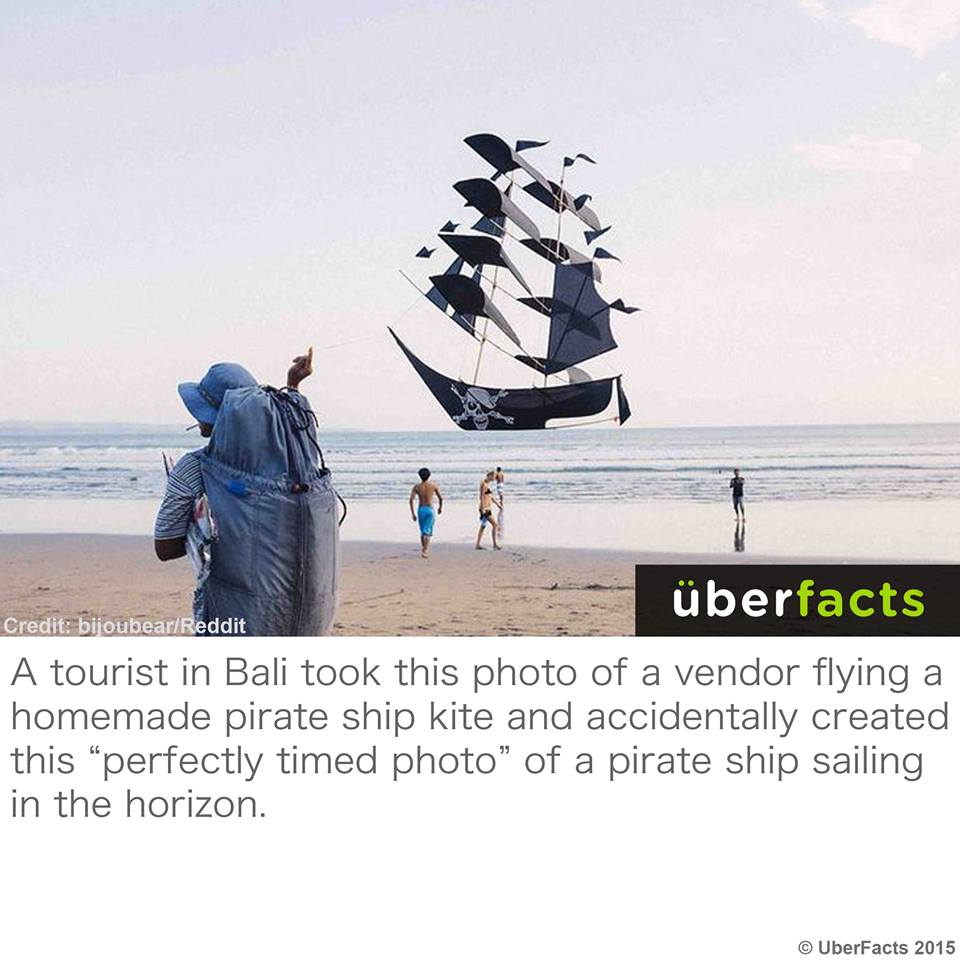 a tourist in bali took this photo of a vendor flying a homemade pirate ship kite and accidentally creates this perfectly timed photo of a pirate ship sailing in the horizon