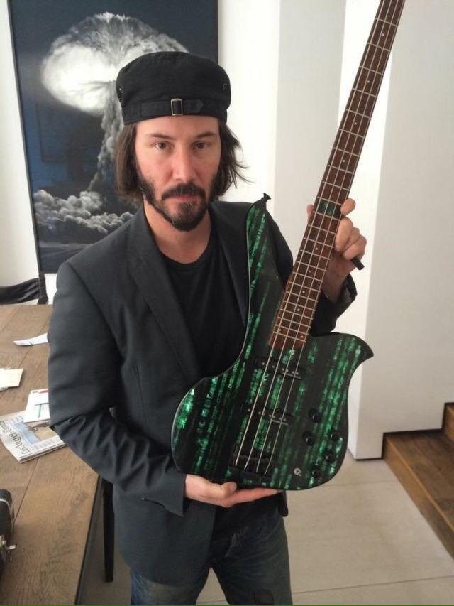 keanu reeves holding a dark matrix guitar