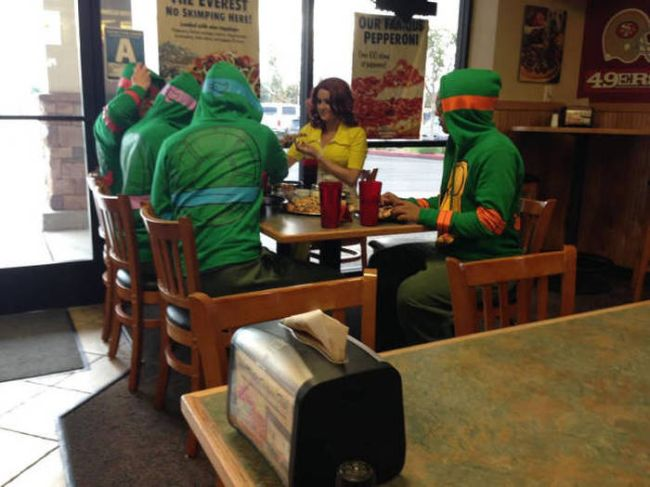 teenage mutant ninja turtles and april oneil eating at a pizza place